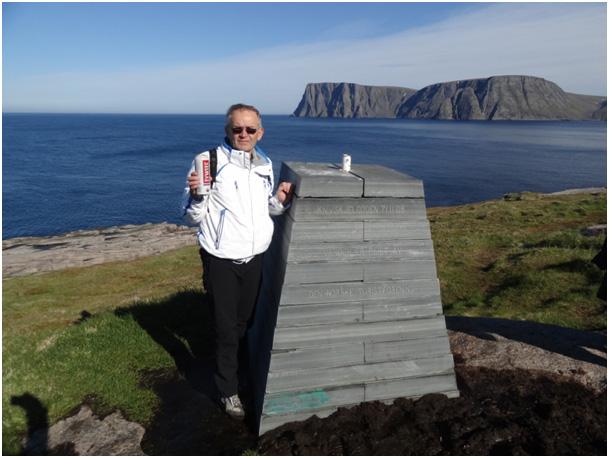 Knivskjellodden zdobyty.  Zasłużony łyk Żywca na końcu Europy. W oddali widok na skałę Nordkapp.